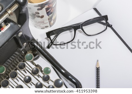 antique typewriter with blank book, pencil and reading glasses on wooden background