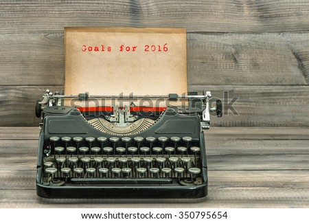 Antique typewriter with grungy paper on wooden background. Goals for 2016. Business concept. Selective focus - stock photo