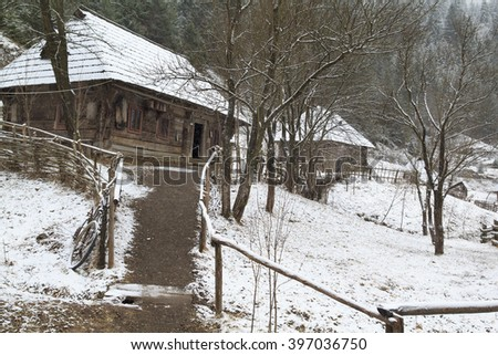 antique ukrainian village in mountains with wooden houses, fence and dry forest around