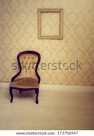 Antique upholstered chair in a wallpapered room with an empty vintage wooden picture frame hanging on the wall suitable as an interior decorating background