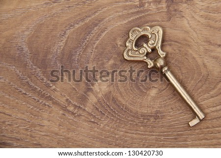 Antique vintage key on wooden background - stock photo