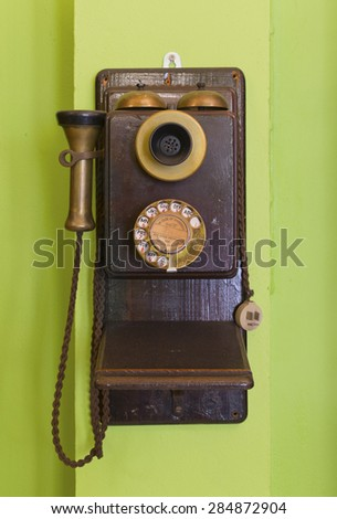 Antique vintage telephone green background.