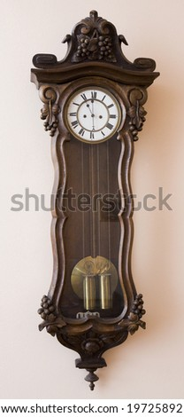 Antique wall clock with a pendulum - stock photo