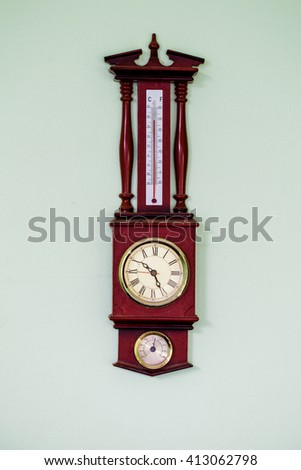 Antique wall clock with a thermometer - stock photo