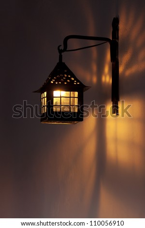 Antique wall lamp glowing orange in the night. Lights and shades patterns on the wall. - stock photo