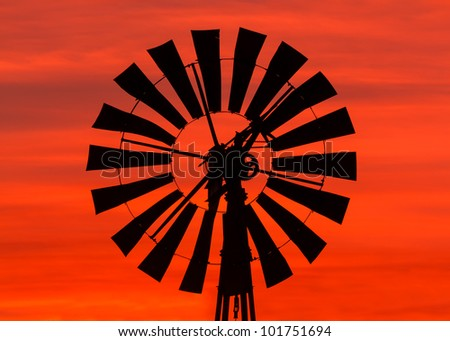 Antique windmill silhouetted by a colorful orange Midwestern sunrise sky - stock photo