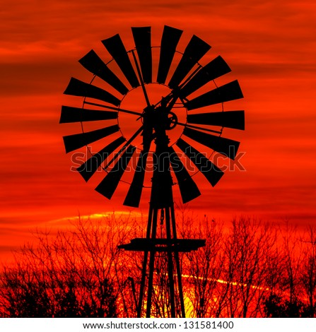 Antique windmill silhouetted by a colorful orange sky. - stock photo