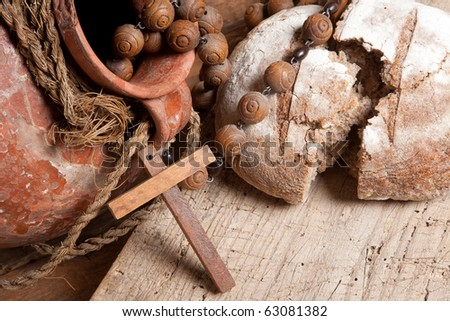 Antique wine jug, rosary and rustic loaf of bread as christian symbols of faith - stock photo