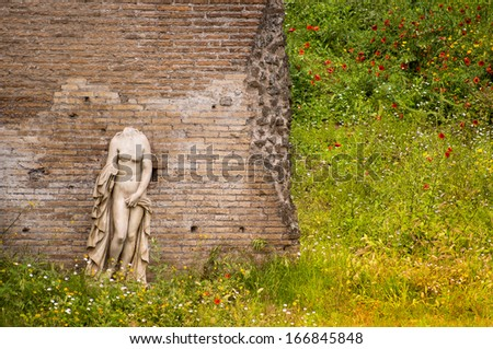 antique woman sculpture against  backdrop of  ruins in Domes  Augustans Garden Palatine Hill in Rome - stock photo
