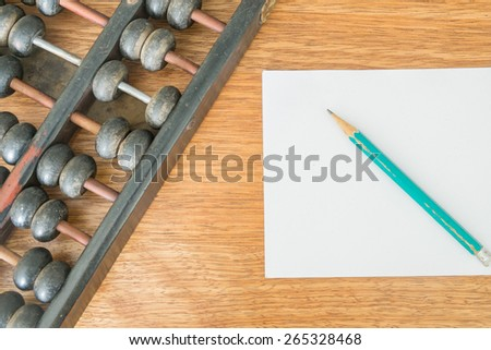 Antique wooden abacus, pencil and paper on a wooden table - stock photo