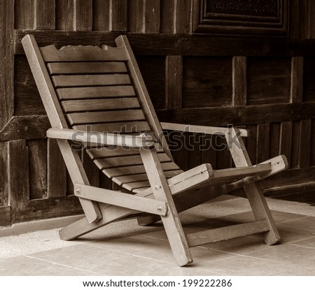 Antique Wooden Arm Chair And Old Wooden Background.