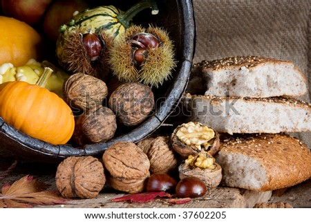 Antique wooden bucket filled with gourds, chestnuts and nuts, and traditional bread on a wooden board - stock photo