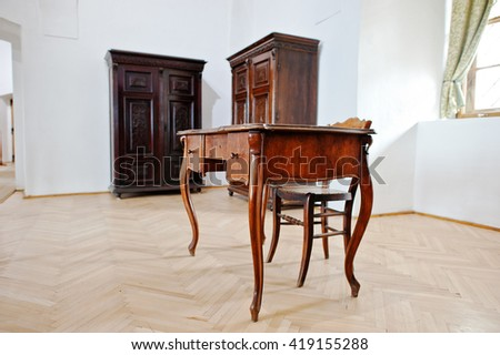 Antique wooden table and chair background of wardrobes - stock photo