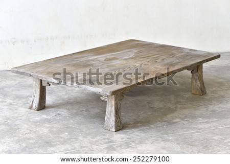 Antique wooden table on the ground - stock photo