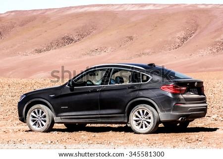 ANTOFAGASTA, CHILE - NOVEMBER 16, 2015: Dirty black crossover BMW F26 X4 in the desert. - stock photo