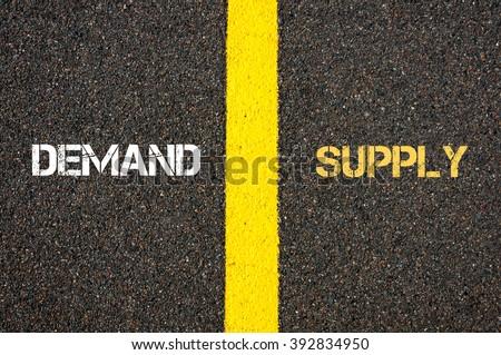 Antonym concept of DEMAND versus SUPPLY written over tarmac, road marking yellow paint separating line between words - stock photo