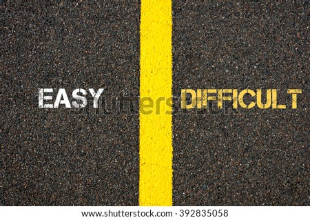 Antonym concept of EASY versus DIFFICULT written over tarmac, road marking yellow paint separating line between words