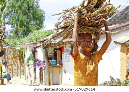 ANTSIRABE, MADAGASCAR, SEPTEMBER 2014, Unknown malagasy boy carrying branches on heads - poverty