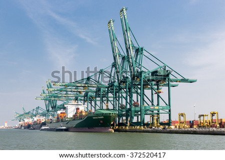 ANTWERP, BELGIUM - AUG 13: Harbor of Antwerp with cargo ships moored at quay with big cranes on August 13, 2015 in the harbor of Antwerp, Belgium