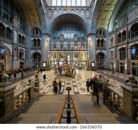 ANTWERP, BELGIUM - DEC 7: People rushing in a symmetrical composition of the main hall of the famous Railway train station, the cathedral amongst stations on December 7, 2013 in Antwerp, Belgium