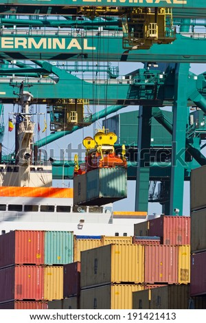 ANTWERP, BELGIUM - JULY 9: Container ship beaing unloaded at the MSC Home terminal July 9,2013 in Antwerp, Belgium. MSC Home terminal is the largest container terminal in the Port of Antwerp