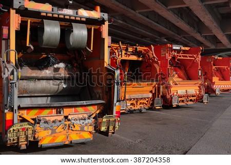 Antwerp, Belgium - June 18, 2015: Garbage trucks parked underneath the motorway bridge, just outside of Antwerp - stock photo
