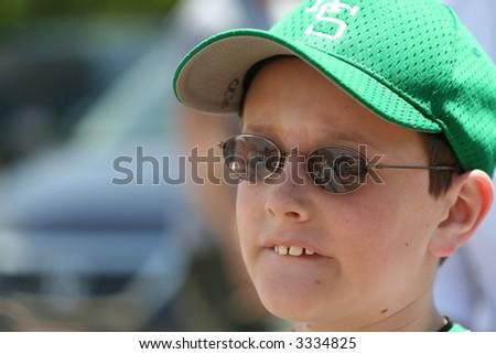 Anxious baseball player bites his lip while waiting to go to bat - stock photo