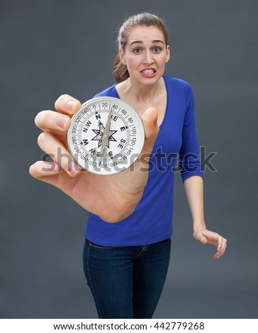 anxious beautiful young woman panicking, holding a large compass, symbol of orientation, held in the foreground, grey background