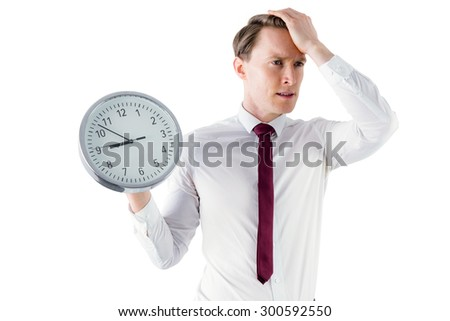 Anxious businessman holding a clock on white background