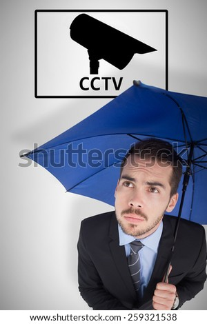 Anxious businessman under umbrella looking up against cctv - stock photo