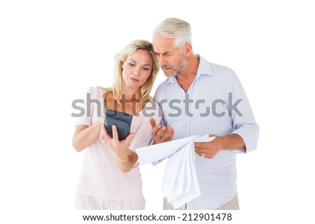 Anxious couple working out their bills on white background - stock photo