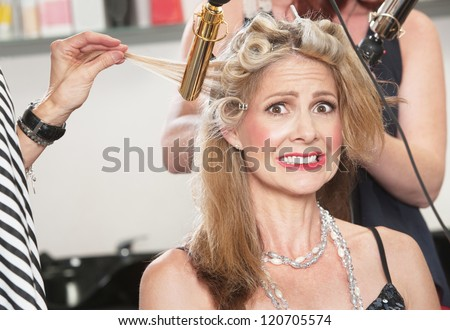 Anxious middle aged white woman with hair stylists working - stock photo