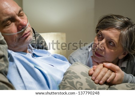 Anxious old woman taking care of sick husband - stock photo