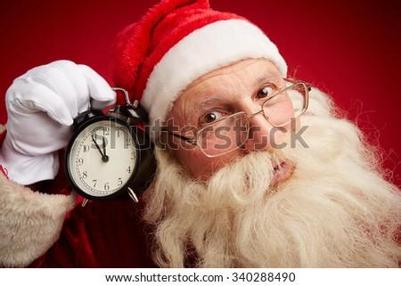 Anxious Santa holding alarm clock by his ear - stock photo
