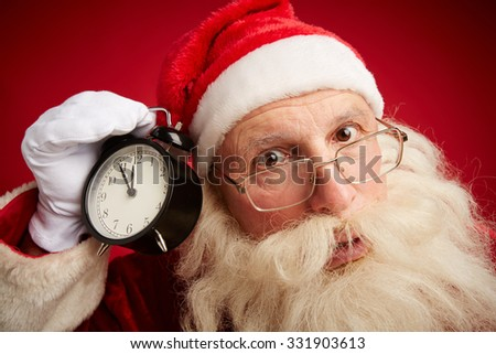 Anxious Santa with alarm clock showing five minutes to xmas