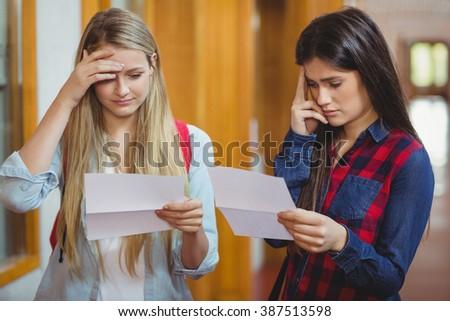 Anxious students looking at results at university - stock photo
