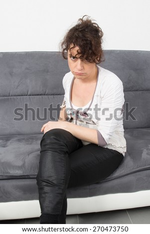 Anxious woman sitting in the living-room at home - stock photo