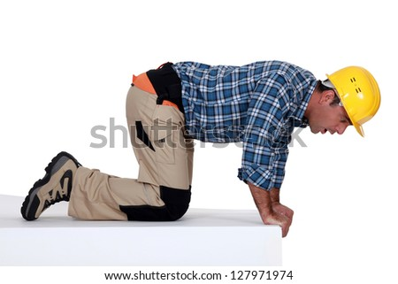 Anxious worker looking over ledge - stock photo