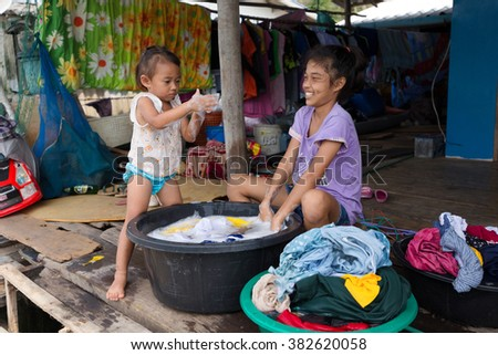 AO SALAT, THAILAND, JANUARY 31, 2016 : Two sisters are hand washing the family laundry in front of the home in Ao Salat fishing village, Ko Kood island, Thailand - stock photo