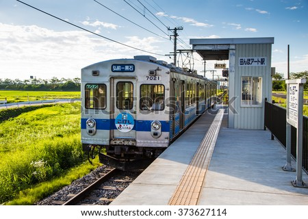 Aomori Japan - 11 Jul 2014: A local train arriving at a small station in the mid of rice field, rural Japan (the end destination station to visit the famous Rice Field Art) - stock photo