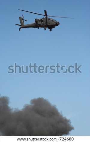 Apache helicopter in flight in a war zone - stock photo