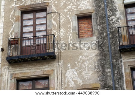 Apartment building with balconies and a stained wall in Barcelona, Spain