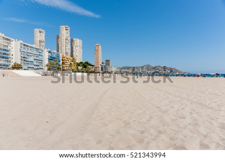 Apartment buildings form long view backdrop to Benidorm beach Spain
