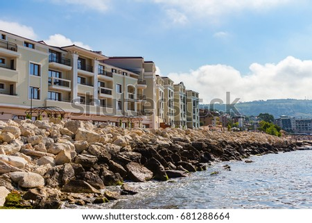 Apartment buildings on seashore with stones in bulgarian city balchik at black sea coast.