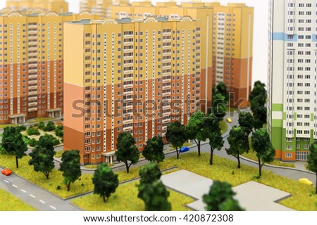 Apartment buildings scale model, residential district layout, mock-up of colorful prefabricated houses with children's playground, trees, grass, roads, sidewalks, driveways, selective focus  - stock photo