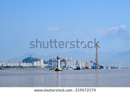 Apartment buildings with river view and industrial maritime equipment, Wenzhou, Zhejiang Province, China - stock photo