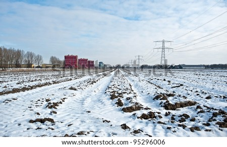 Apartments along a snowy field in winter - stock photo