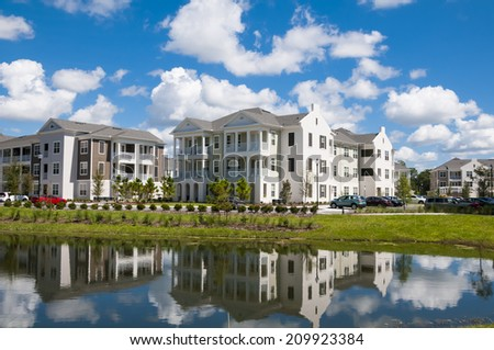 Apartments and Condos with reflection in a nearby lake and partly cloudy blue sky - stock photo