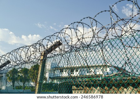 Apartments building protected against criminals with fences and razor wires - stock photo
