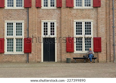 Apeldoorn, Netherlands - October 31, 2014: visitor sits on bench at Het Loo Palace in Apeldoorn. - stock photo